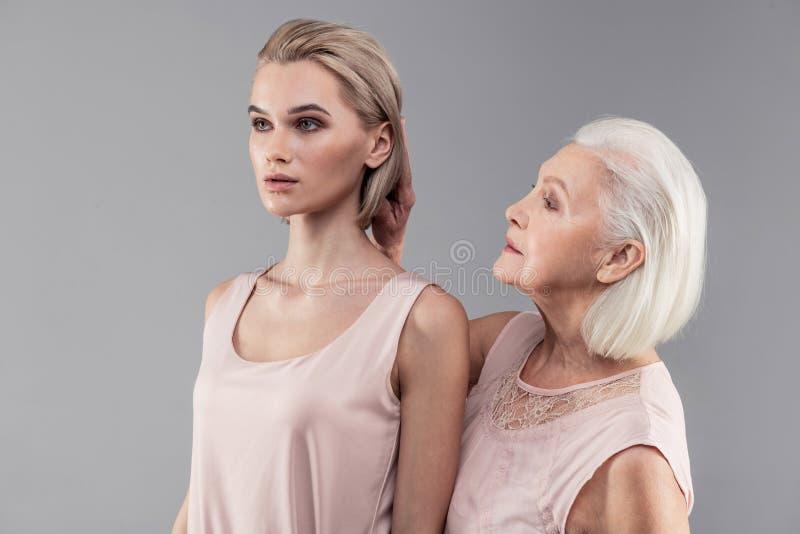 Troskliwa starsza siwowłosa kobiety odświeżenia koczka fryzura jej córka zdjęcie stock