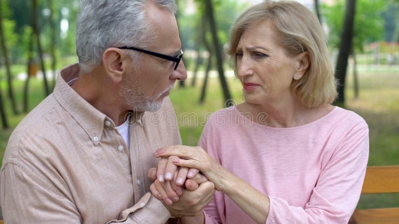 Troskliwe męża mienia ręki stara chora żona, Alzheimer choroba, rodzinny poparcie fotografia stock