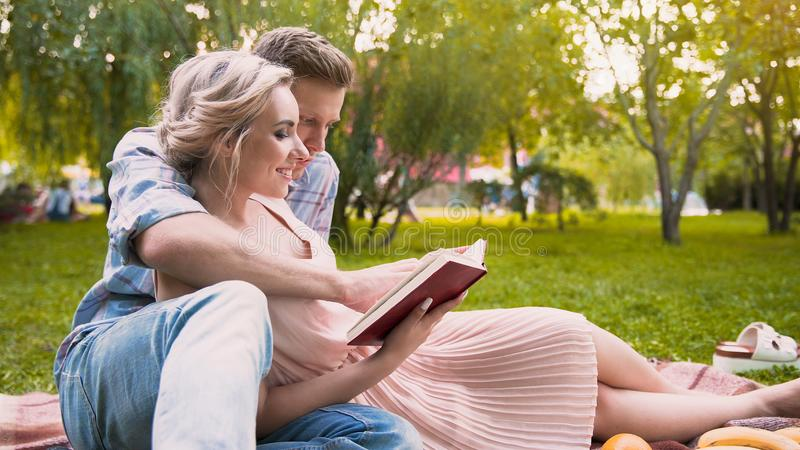 Troskliwego faceta czytelnicza opowieść jego piękna dama, delikatnie ściska ona, data w parku obraz royalty free