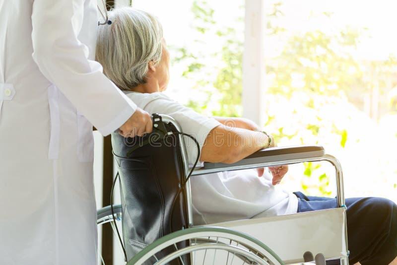 Troskliwy lekarki lub pielęgniarki zachęcanie obezwładniający, Alzheimer starsza azjatykcia kobieta na wózku inwalidzkim, żeński  obraz stock