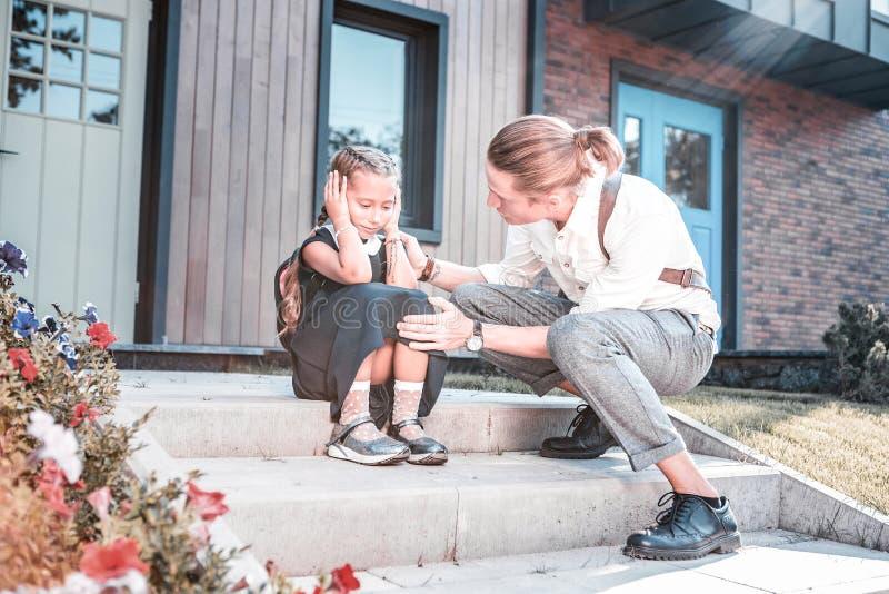 Troskliwy ojciec uspokaja jego małego ślicznego córki uczucie martwił się przed szkołą zdjęcie stock