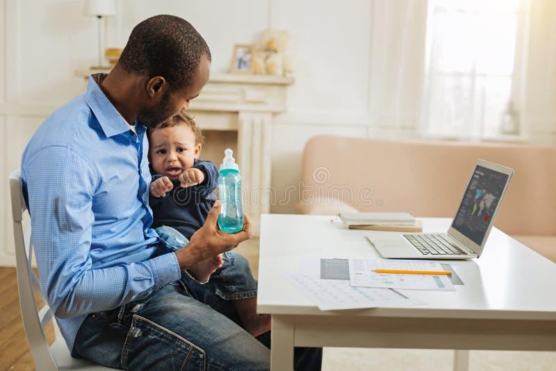 Troskliwy ojczulek trzyma jego syna i dziecka butelkę fotografia stock