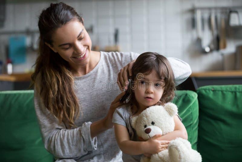 Troskliwych kochających macierzystych szczotkować dzieciaka córek włosiany obsiadanie na kanapie fotografia stock