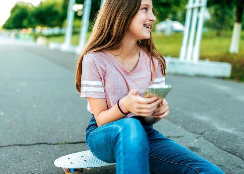 Troszkę dziewczyny uczennica 12-16 lat na ulicie, siedzi na deskorolka w lecie w parku W rękach telefon obrazy royalty free
