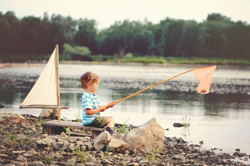 Troszkę łowi na jeziorze w sammer chłopiec obraz royalty free