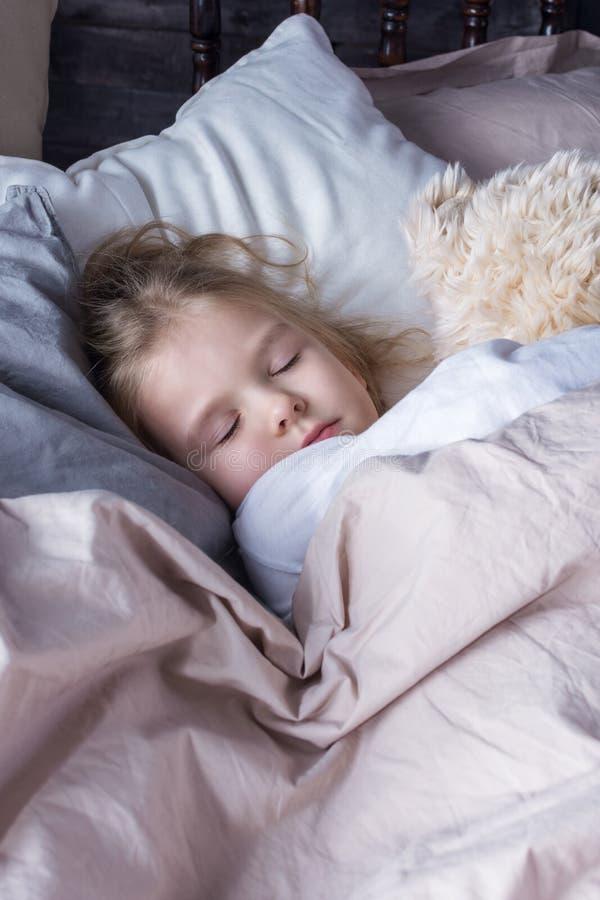Troszkę śpi mocno w łóżku dziewczyna z blondynem Dziecko ściska niedźwiedzia zdjęcia royalty free