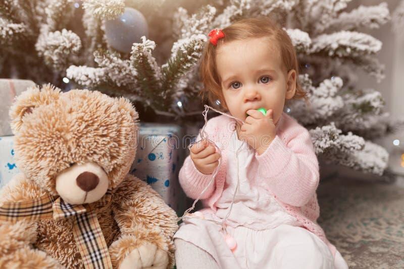 Troszkę bawić się z girlandą z nowego roku drzewem dziewczyna niebezpieczeństwo Niepodporządkowany dziecko Dobry nowego roku duch obraz royalty free
