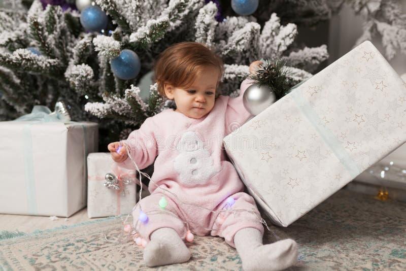 Troszkę bawić się z girlandą z nowego roku drzewem dziewczyna niebezpieczeństwo Niepodporządkowany dziecko Dobry nowego roku duch zdjęcia royalty free