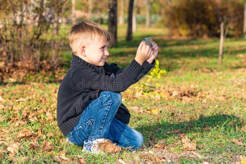 Troszkę bierze obrazki na telefonie w parku na słonecznym dniu chłopiec zdjęcie royalty free
