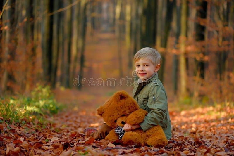 Troszkę chłopiec bawić się w jesień parku fotografia royalty free