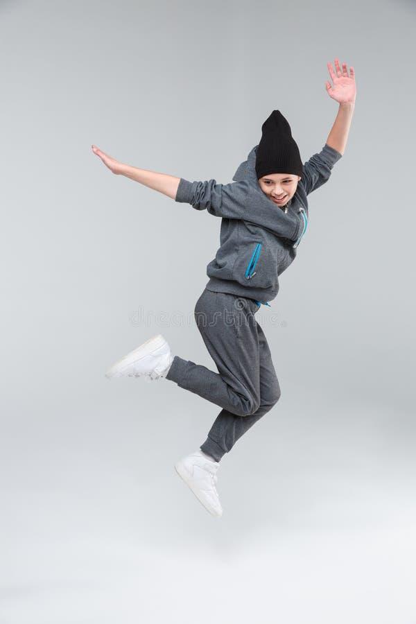 Troszkę chłopiec dancingowe skokowe oddolne trzyma mocno nogi i podnosić ręki na szarym tle zdjęcie royalty free
