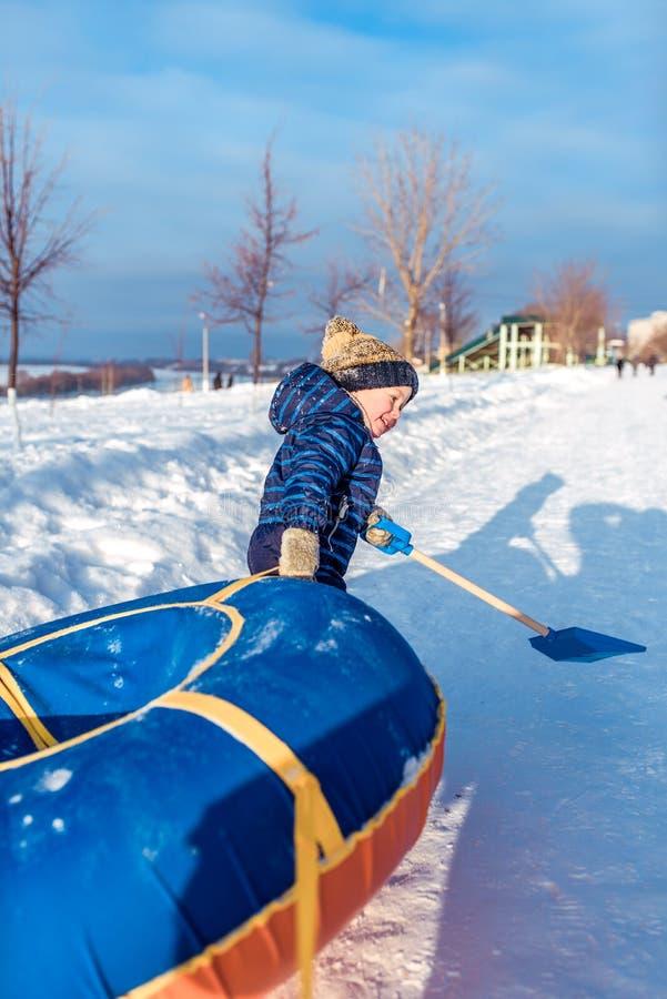 Troszkę chłopiec 3 lat w zimie na ulicie, wlec tubing, dla jechać od wzgórza w rękach, dzieci fotografia royalty free