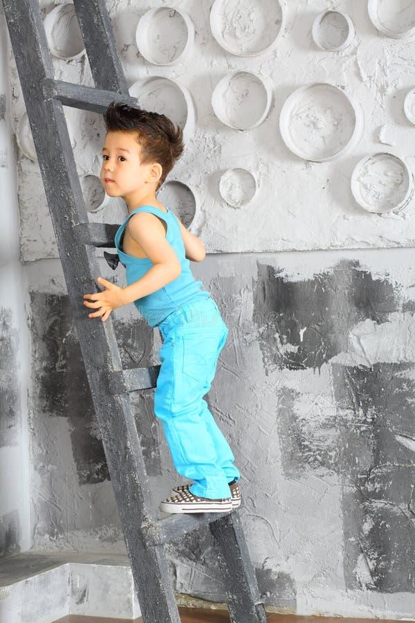 Troszkę chłopiec stojaki na drabinie obrazy royalty free