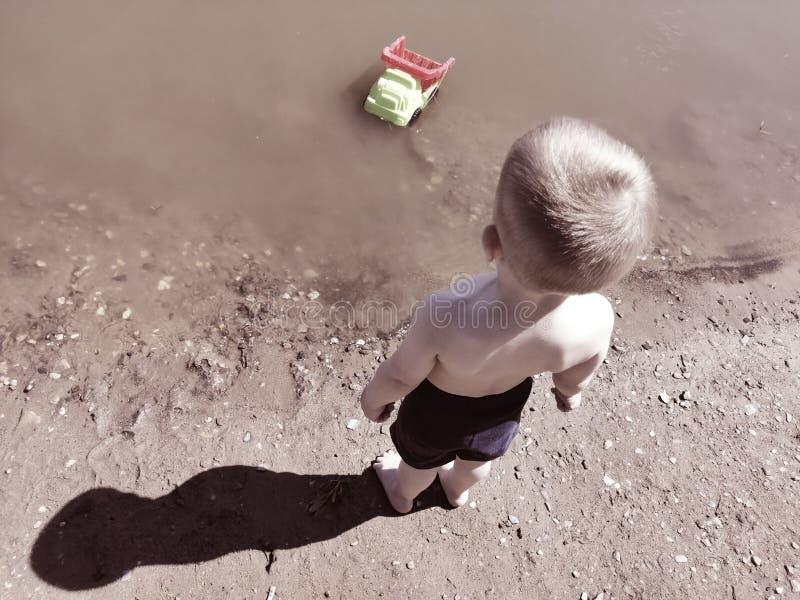 Troszkę chłopiec stojaki na plaży i spojrzenia przy maszyną obraz royalty free