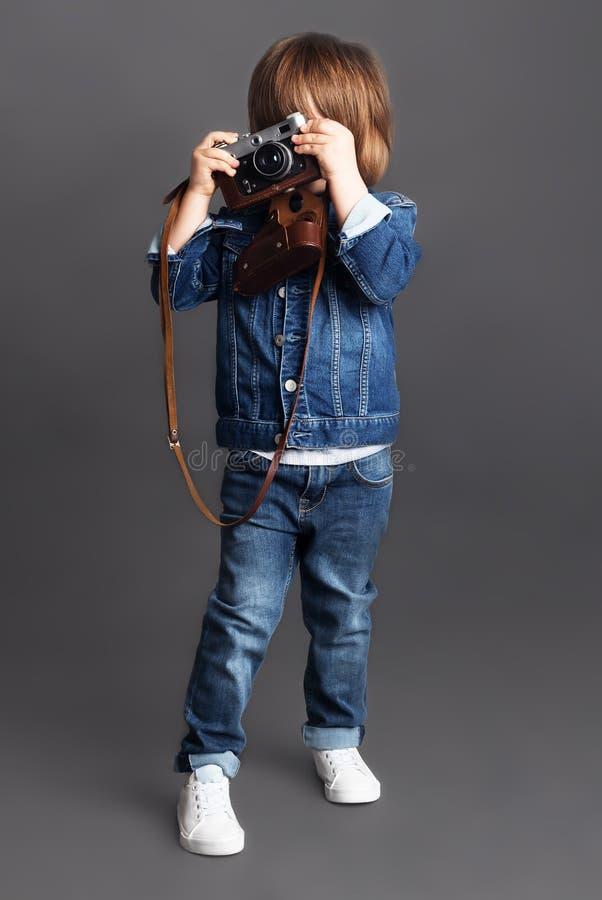 Troszkę chłopiec w drelich próbach brać krótkopędu używać rocznik kamerę zdjęcia stock