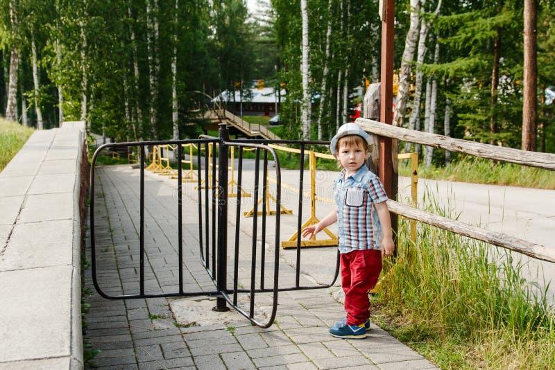 Troszkę chłopiec w koszula i kapeluszu stojakach blisko kołowrotu w lecie zdjęcie royalty free