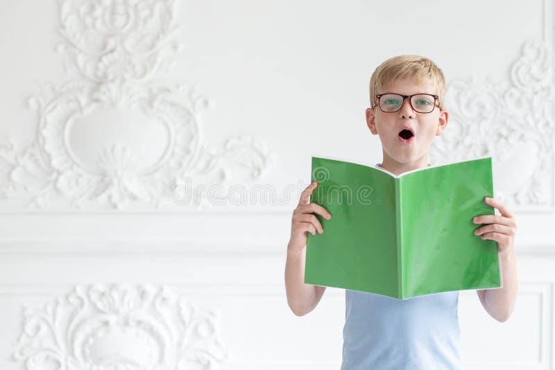 Troszkę czyta głośno tekst od jego książki na tle biel ściana uczeń w szkłach zdjęcia royalty free