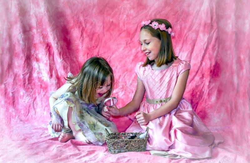 Troszkę dziewczyn spojrzenia w lustrze trzymającym jej dużą siostrą obraz royalty free