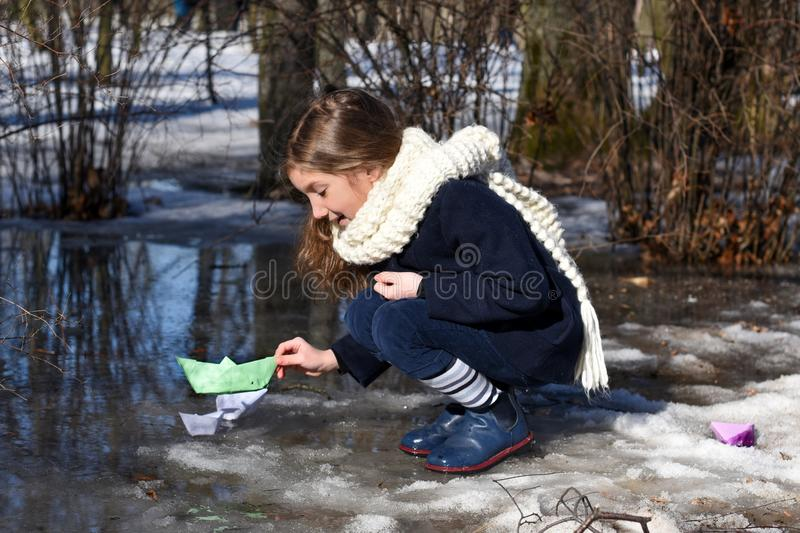Troszkę dziewczyna bawić się z papierowymi łodziami w wczesna wiosna marznąć kałużach zdjęcie stock