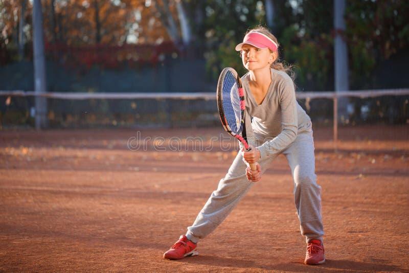 Troszkę dziewczyna, gracz w tenisa stoi w pozie i trzyma tenisowego kant, zdjęcia royalty free