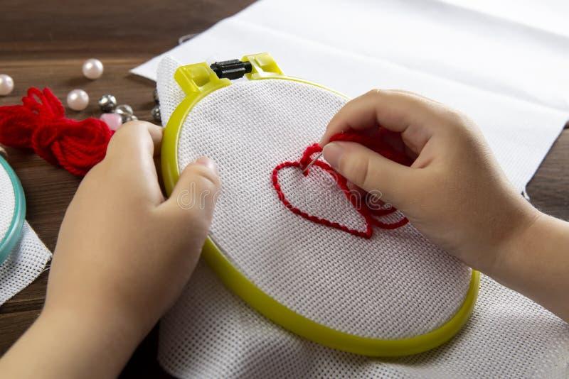 Troszkę haftuje serce na widoku białych sukiennych akcesoriach dla broderii na drewnianym tle z góry dziewczyna obrazy stock