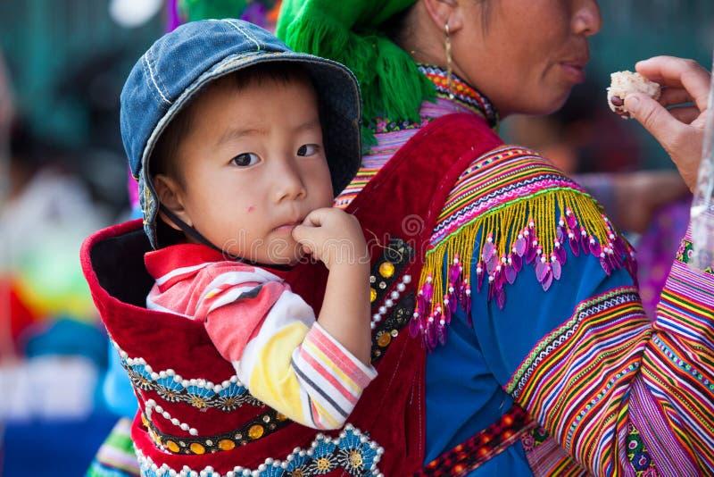 Troszkę Hmong dziecko na jego matce z powrotem (Miao) zdjęcia stock