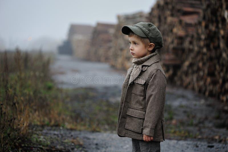 Troszkę jest trwanie i patrzejąca naprzód w mgłowym dniu chłopiec obrazy stock