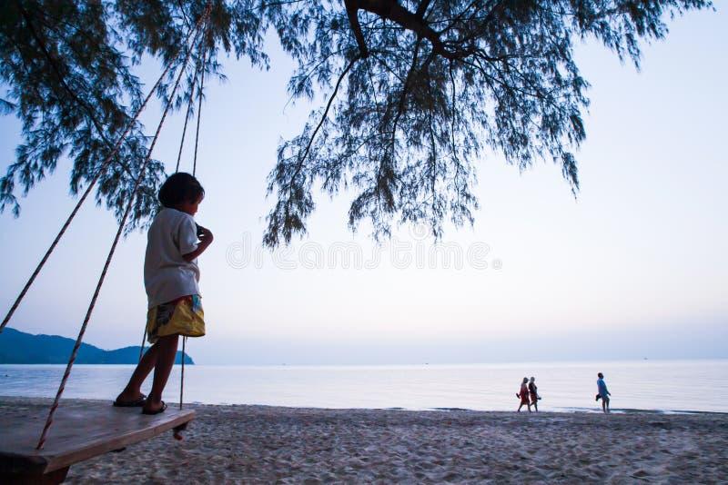 Troszkę lokalna dziewczyny pozycja na huśtawce i patrzeć grupy europejscy turyści chodzi na plaży przy zmierzchem zdjęcia stock