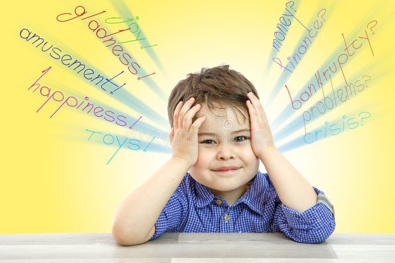 Troszkę myśleć o niezrozumiałych problemach, siedzi chłopiec na odosobnionym tle i zdjęcie stock