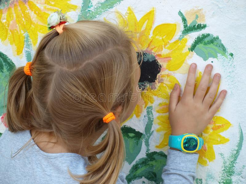 Troszkę obwąchuje żółtych słoneczniki malujących na białej ścianie dziewczyna i fotografia royalty free
