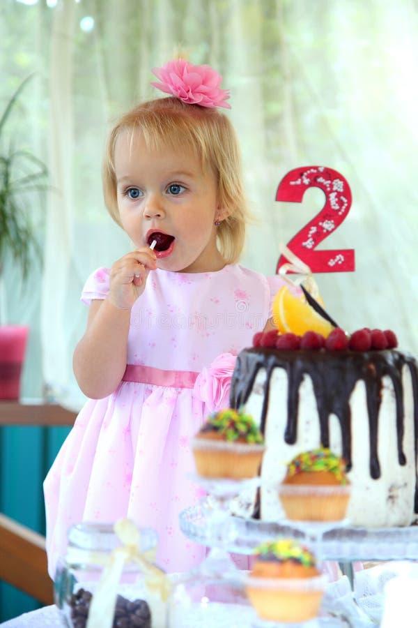 Troszkę próbuje urodzinowego tort białogłowa dziewczyna dwa roku Małej dziewczynki odświętności po drugie urodziny zdjęcia stock