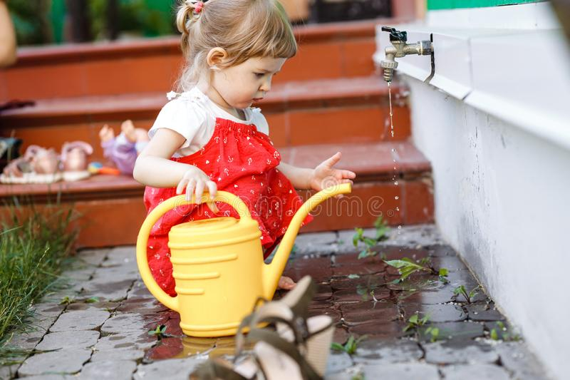 Troszkę rysuje wodę w podlewanie puszce w ogródzie obok domu na letnim dniu dziewczyna ubierająca w sundress obraz stock