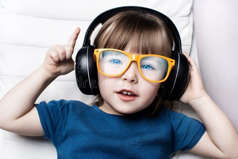 Troszkę słucha muzyka na hełmofonach w karle dom dziewczyna w pomarańczowych modnisiów szkłach obrazy royalty free
