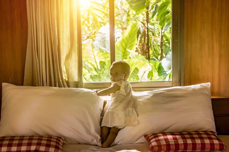 Troszkę stoi na łóżku przeciw tłu okno dziecięca dziewczynka w białej sukni za którym dżungla A obraz royalty free