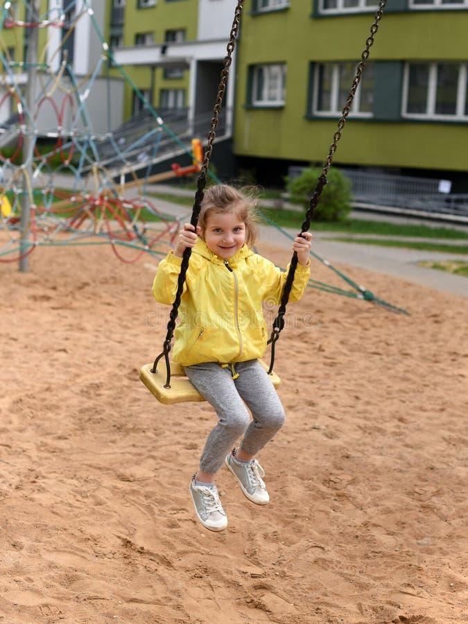 Troszkę uśmiechać się dziewczyny cieszy się huśtać się w boisku mieszkanie domu ` s sądu jard zdjęcia stock