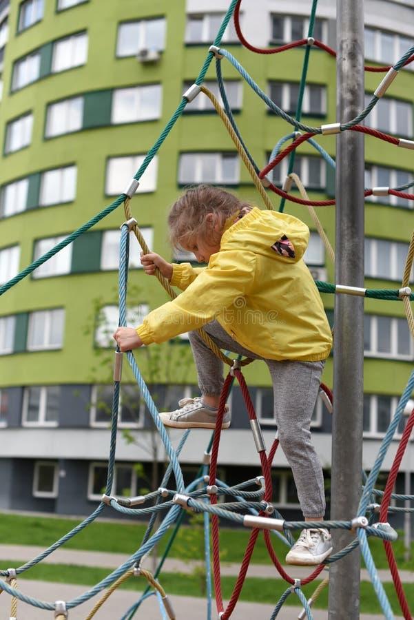 Troszkę uśmiechać się dziewczyny używa sporta wyposażenie w boisku mieszkanie domu ` s sądu jard obraz royalty free