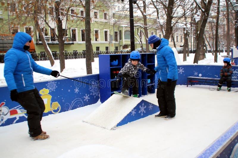 Troszkę uczy się jechać snowboard na Tverskoy bulwarze chłopiec zdjęcie stock