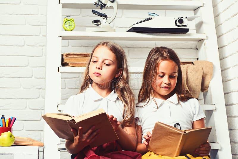 Troszk? ?liczne dziewczyny w jednolitym czytaniu ksi??kowy obsiadanie na drabinie obrazy royalty free