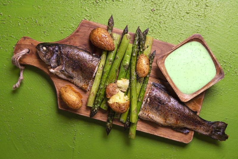 Trota al forno con asparago e salsa verde fotografia stock libera da diritti