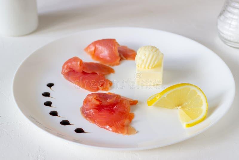 Trota, burro e limone su un piatto Priorit? bassa bianca fotografia stock libera da diritti
