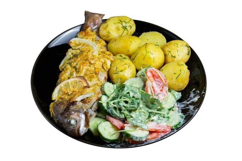 Trota cotta su un piatto con un'insalata della rucola, dei pomodori, dei cetrioli e di giovani patate con aneto isolato su fondo  fotografie stock