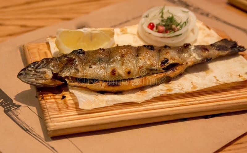 Trota del pesce per la cena, su un piatto di legno fotografie stock
