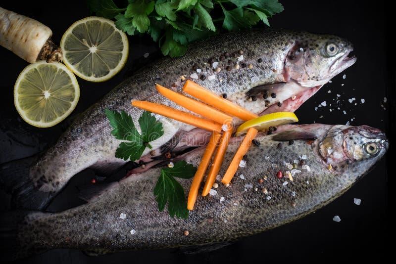 Trota fresca con le spezie, le erbe, il limone ed il sale marino fotografia stock libera da diritti