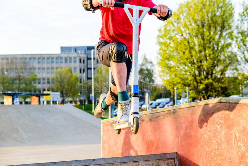 'trotinette' adolescente da equitação do menino da opinião do dia no campo de jogos de patinagem fotografia de stock