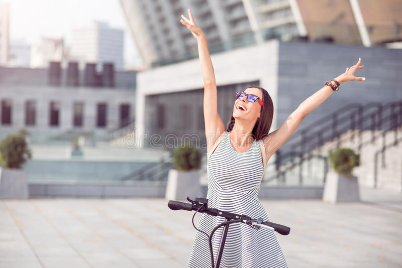 'trotinette' alegre do pontapé da equitação da mulher imagens de stock