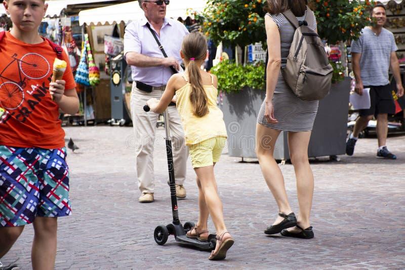 'trotinette' alemão do pontapé da equitação da menina com visita e curso de passeio da mãe no mercado velho da cidade de heidelbe fotografia de stock