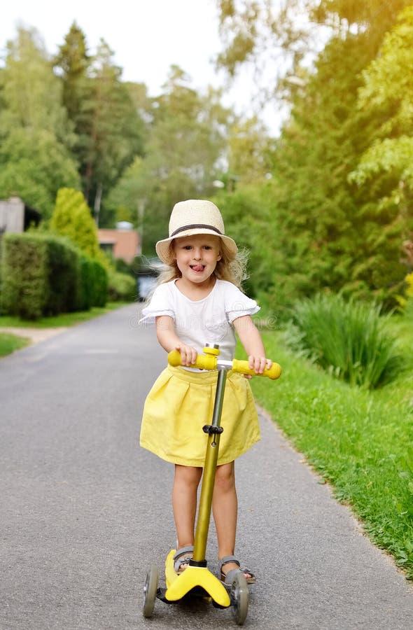 'trotinette' branco exterior, capacete do pontapé da equitação da camisa da saia feliz do amarelo da menina de segurança cor-de-r foto de stock royalty free