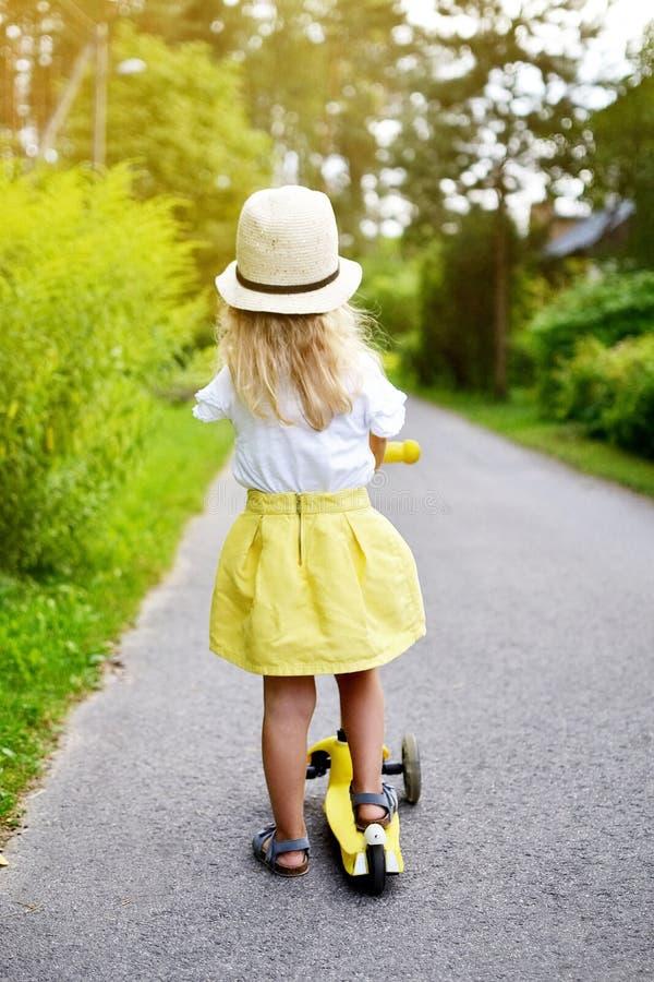 'trotinette' branco exterior, capacete do pontapé da equitação da camisa da saia feliz do amarelo da menina de segurança cor-de-r fotos de stock royalty free