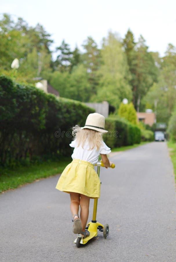 'trotinette' branco exterior, capacete do pontapé da equitação da camisa da saia feliz do amarelo da menina de segurança cor-de-r imagem de stock royalty free