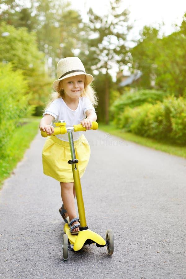 'trotinette' branco exterior, capacete do pontapé da equitação da camisa da saia feliz do amarelo da menina de segurança cor-de-r fotografia de stock